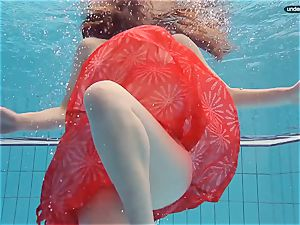 crimson clothed nubile swimming with her eyes opened